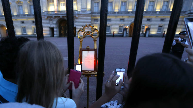 People take pictures of a notice proclaiming the birth of a baby boy to Prince William and Kate, Duchess of Cambridge on display for public view at Buckingham Palace in London, Monday, July 22, 2013. (AP Photo/Sang Tan)