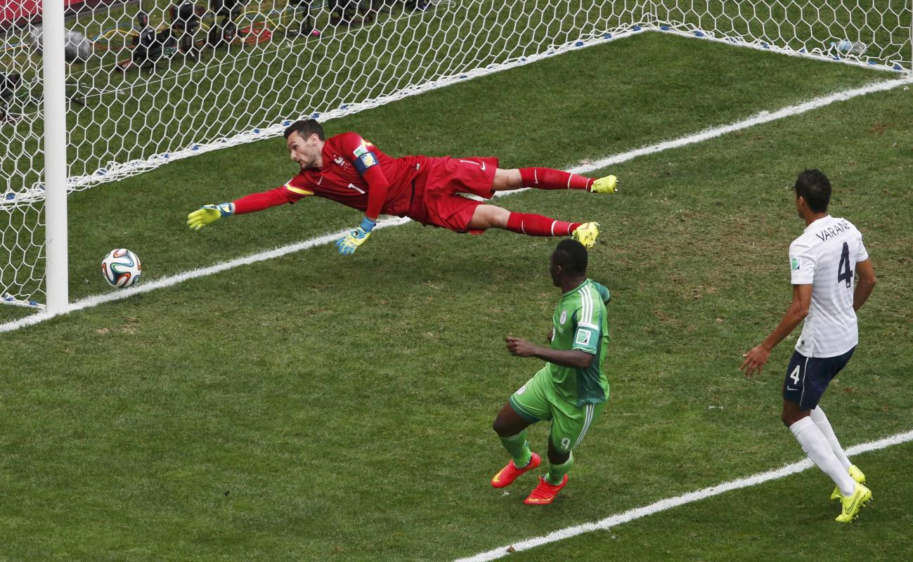 Nigeria's Emenike kicks to score a goal against France's goalkeeper Lloris, which was later ruled offside and disallowed, during their 2014...