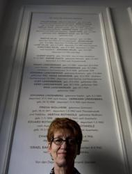 Berlin tenant Gabrielle Pfaff stands last month in front of a plaque commemorating Jews evicted during the Nazi era from the building in which she lives. Thanks to the efforts of a group of Berliners to trace the Jewish residents who once lived in their building, the victims are finally being openly remembered