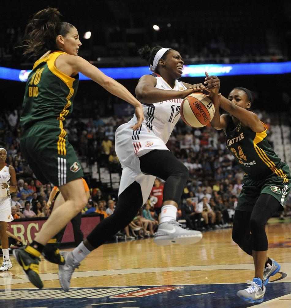 Connecticut Sun's Chelsea Gray, center, is fouled by Seattle Storm's Jewell Loyd, right, as Storm's Sue Bird, left, defends, during the first half of a WNBA basketball game, Friday, July 31, 2015,