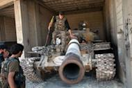 Rebels inspect a T-72 tank parked in a secret location in the northwestern Syrian province of Idlib, on June 22, 2013