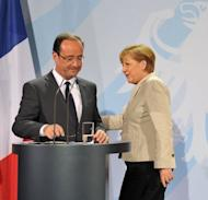 New French president Francois Hollande and German chancellor Angela Merkel at their joint press conference at the German Chancellery in Berlin. Merkel and Hollande Tuesday stressed a shared desire to keep Greece in the eurozone, with the new French president adding that all options must be kept open in confronting the crisis