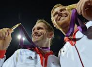 Germany's Jonas Reckermann (R) and Julius Brink (L) pose with their gold medals after winning against Brazil in the men's beach volleyball final match on The Centre Court at Horse Guards Parade in London during the London 2012 Olympics Games
