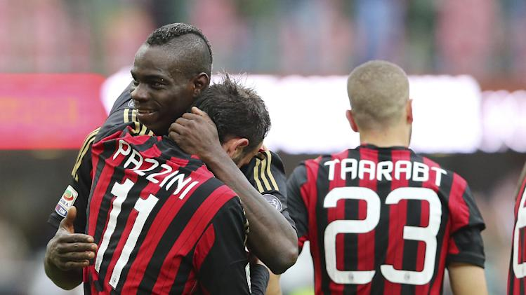AC Milan forward Giampaolo Pazzini, foreground, celebrates with his teammates forward Mario Balotelli, left, and Adel Taarabt, of Morocco, after scoring during the Serie A soccer match between AC Milan and Livorno at the San Siro stadium in Milan, Italy, Saturday, April 19, 2014
