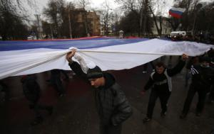 Pro-Russian demonstrators march with a huge Russian…