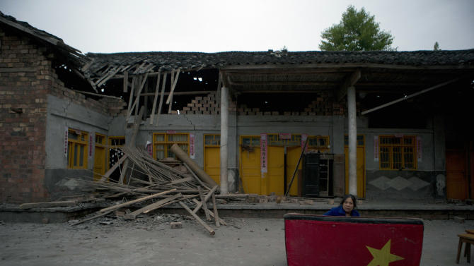 Zheng Xianlan, a 58-year-old corn farmer, awakens after spending the night sleeping on a sofa outside her house which was damaged by an earthquake near Shangli town in southwestern China's  Sichuan province, Sunday, April 21, 2013. Residents awoke Sunday after spending the night outdoors or in their cars in the town near the epicenter of a powerful earthquake that struck the steep hills of China's southwestern Sichuan province, leaving at least 160 people dead and more than 6,700 injured. (AP Photo/Ng Han Guan)