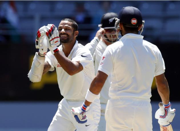 India's Shikhar Dhawan celebrates scoring a century during his second innings on day four of the first international test cricket match against New Zealand