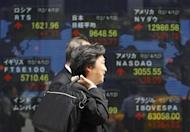 Men walk past an electronic board displaying market indices from around the world outside a brokerage in Tokyo