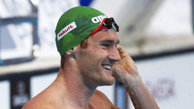 van der Burgh of South Africa celebrates after setting a new world record in the men's 50m breaststroke preliminaries at the Aquatics World Championships in Kazan