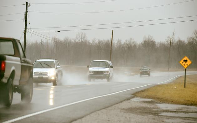 Traffic and high winds kick up water spray as motorists travel US 60 near Waverly, Ky. Wednesday morning, March 4, 2015. Kentuckians are dealing with flooded roadways and mudslides as they brace for a