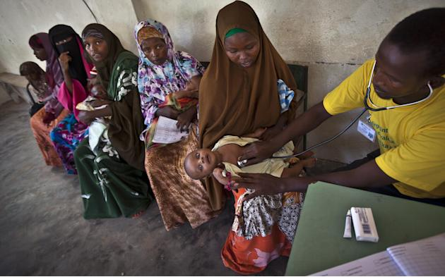FILE - In this Wednesday, April 24, 2013 file photo, Somali mothers wait in line to have their babies examined before receiving a five-in-one vaccine against several potentially fatal childhood diseas