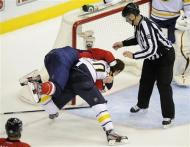Washington Capitals left wing Troy Brouwer, top, fights with Buffalo Sabres defenseman Christian Ehrhoff, bottom, as linesman Scott Cherrey (50) looks on during the first period of an NHL hockey game, Friday, Dec. 30, 2011, in Washington. (AP Photo/Nick Wass)