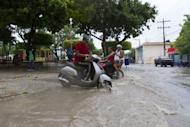 Local residents stay under the rain in Enriquillo, southwestern Dominican Republic. Tropical Storm Isaac gained strength as it roared towards the Domincan Republic and Haiti, where it was to make landfall later in the day, threatening survivors of a devastating 2010 earthquake