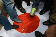 Anti-Japan activists step on a Japanese flag during a protest in front of the parliament building in Taipei to demand the Taiwan government to cooperate with China against Japan. A swathe of Japan's biggest corporate names padlocked factories in China as violent anti-Japan protests sparked safety fears, and threatened economic ties worth more than $300 billion a year