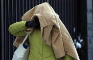 A woman covers her head with a jacket as she walks in frigid cold temperatures though downtown Chicago, Illinois, January 6, 2014. REUTERS/Jim Young