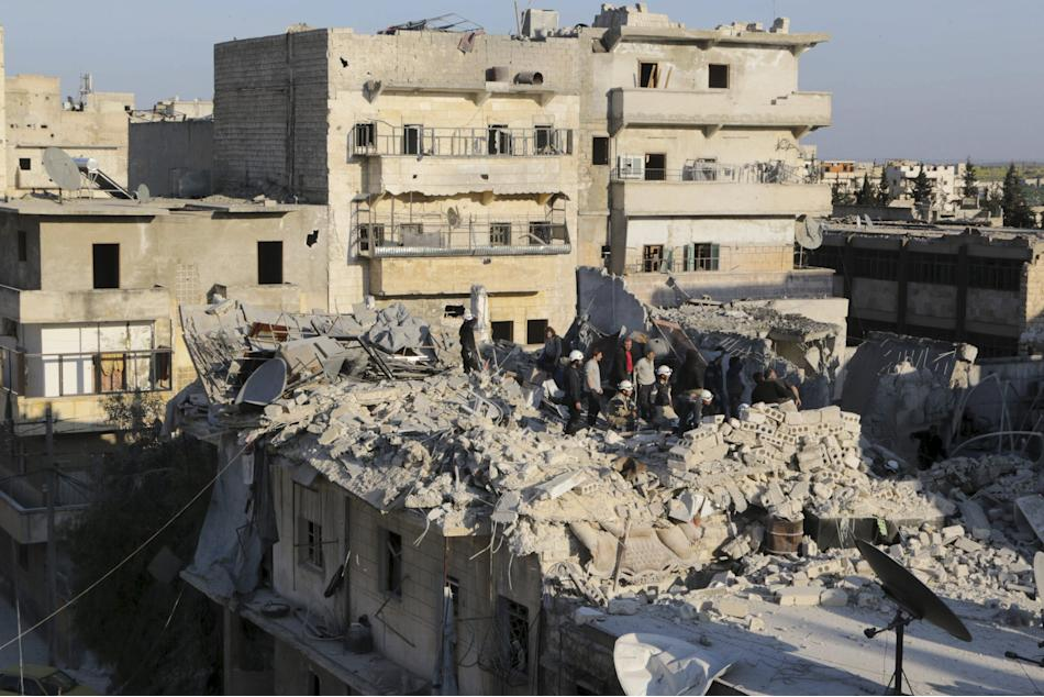 Residents and civil defence members look for survivors amid debris after what activists said were barrel bombs dropped by forces loyal to Syria's president Bashar Al-Assad in al-Katerji district i