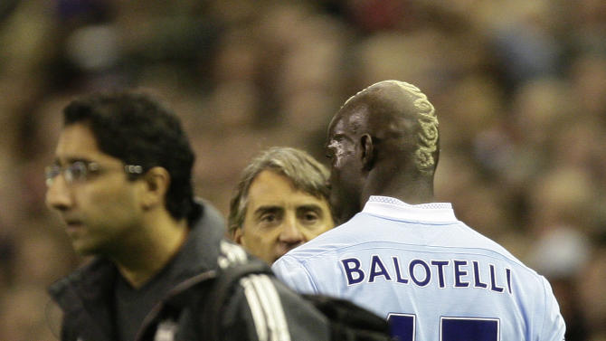 Manchester City's Mario Balotelli, right, stands with manager Roberto Mancini after being sent off by referee Martin Atkinson following a second yellow card during his team's 1-1 draw against Liverpool in their English Premier League soccer match at Anfield Stadium, Liverpool, England, Sunday Nov. 27, 2011. (AP Photo/Jon Super)