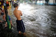 Children watch a flooded street after a sudden heavy downpour in Manila in September. Floods have become three times more frequent across the Asia-Pacific in the past 30 years, the Asian development Bank says