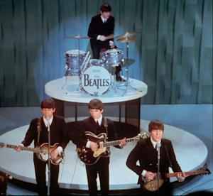 """FILE - The Beatles perform at the """"Ed Sullivan Show,"""" in New York in this Feb. 9, 1964 file photo.  Universal Music Group can buy the famed British music company EMI, including the hugely lucrative Beatles catalogue, the European Union's competition regulator said Friday Sept 21 2012, but must jettison some of the famed label's other big acts, including Coldplay and Pink Floyd.  (AP Photo)"""