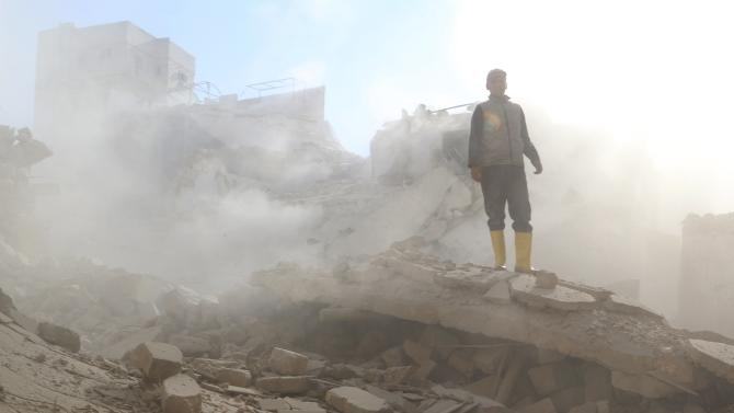 A man stands on rubble of damaged buildings at a site hit by what activists was a barrel bomb dropped by forces loyal to Syria's President Bashar al-Assad at Qadi Askar district of Aleppo