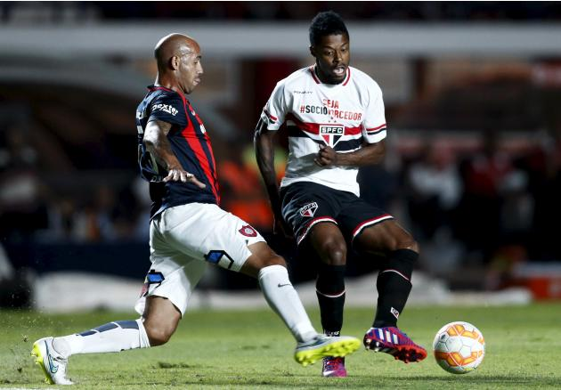 Bastos of Brazil's Sao Paulo and Mercier of Argentina's San Lorenzo fight for the ball watches during their Copa Libertadores soccer match in Buenos Aires