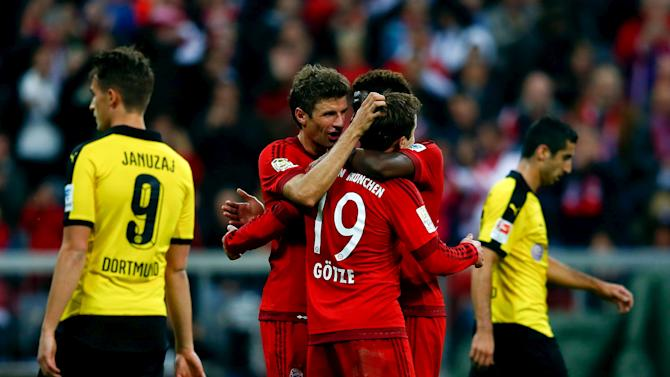 Thomas Mueller, Mario Goetze and David Alaba of FC Bayern Munich celebrate a goal against Borussia Dortmund during their German first division Bundesliga soccer match in Munich