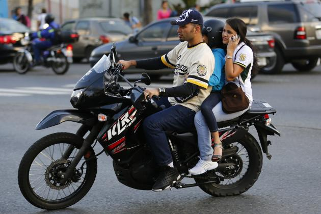 "A family rides on a motorcycle among the traffic in Caracas October 25, 2013. Choking traffic, causing pileups and even ambushing drivers, Venezuela's hordes of motorcyclists are an increasingly high-profile problem for the new government of President Nicolas Maduro. Denounced in the media as a ""plague,"" they provide essential, cheap transport but are often held responsible for anarchy on the roads and the terrifying number of homicides, kidnappings and armed robberies that beset the South American country. Picture taken October 25, 2013. To match Feature VENEZUELA-BIKERS/ REUTERS/Jorge Silva (VENEZUELA - Tags: SOCIETY TRANSPORT)"
