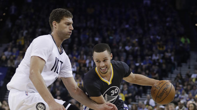 Golden State Warriors' Stephen Curry (30) dribbles past Brooklyn Nets' Brook Lopez during the first half of an NBA basketball game Saturday, Feb. 25, 2017, in Oakland, Calif. (AP Photo/Marcio Jose Sanchez)