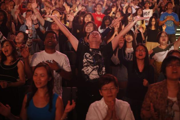 """Worshippers attend a church service at the City Harvest Church in Singapore March 1, 2014. With a """"prosperity gospel"""" that blends the spiritual and the material, City Harvest and other Pentecostal megachurches in the wealthy Asian city-state have perfected a popular and lucrative model. Now they are working to export it to the world and turn Singapore into a hub for evangelical Christianity. Picture taken March 1, 2014. To match Feature SINGAPORE-MEGACHURCHES/ REUTERS/Edgar Su (SINGAPORE - Tags: RELIGION)"""