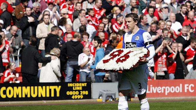 FILE - This Saturday, April 11, 2009, file photo shows Blackburn Rovers' Stephen Warnock carrying flowers in memory of the 96 victims of the Hillsborough disaster before their English Premier League soccer match against Liverpool at Anfield Stadium, Liverpool, England. Ninety-six Liverpool supporters were crushed to death at Hillsborough Stadium at an FA Cup semifinal in 1989, a disaster that deeply scarred the city of Liverpool but which fans from rival teams have since twisted into chants too horrible to repeat.(AP Photo/Paul Thomas, File)