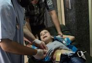 A wounded Syrian boy cries as he is treated at a hospital after being shot by a sniper in the northern city of Aleppo