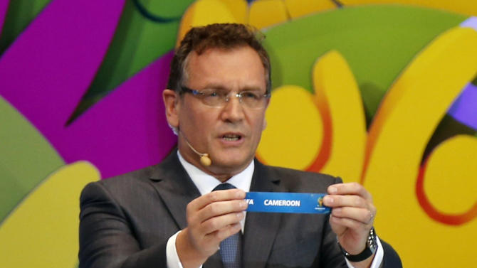 "FIFA Secretary General Jerome Valcke holds the slip showing ""Cameroon"" during the draw for the 2014 World Cup at the Costa do Sauipe resort in Sao Joao da Mata"