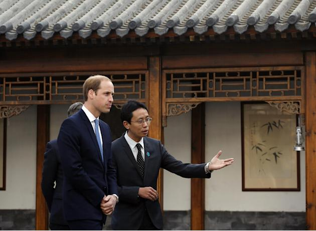 Britain's Prince William, left, is guided by Matthew Hu, China representative of the Prince's School of Traditional Arts while he visits the Shijia Hutong in Beijing Monday, March 2, 2015. (AP