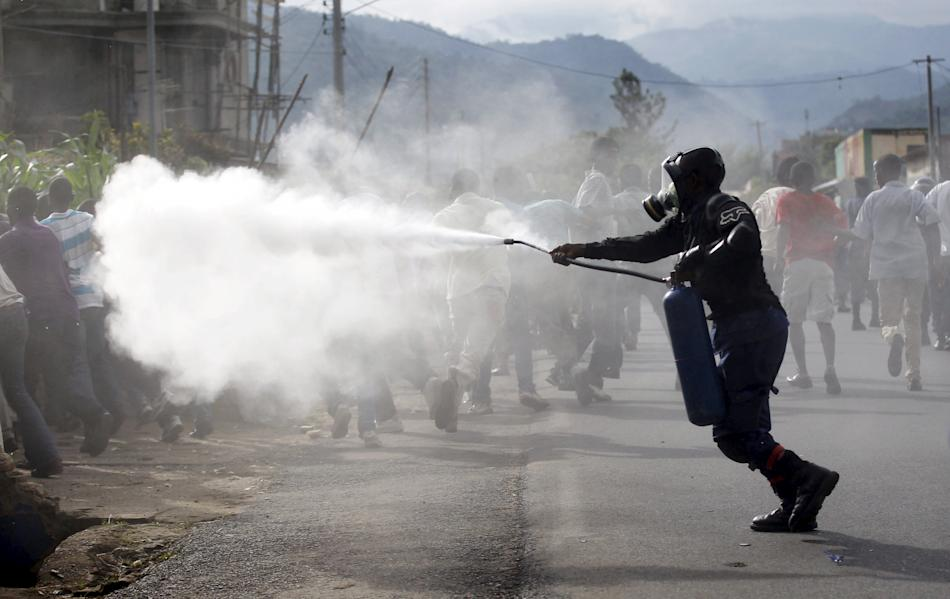 Riot police officer sprays teargas on residents participating in street protests in Burundi's capital Bujumbura