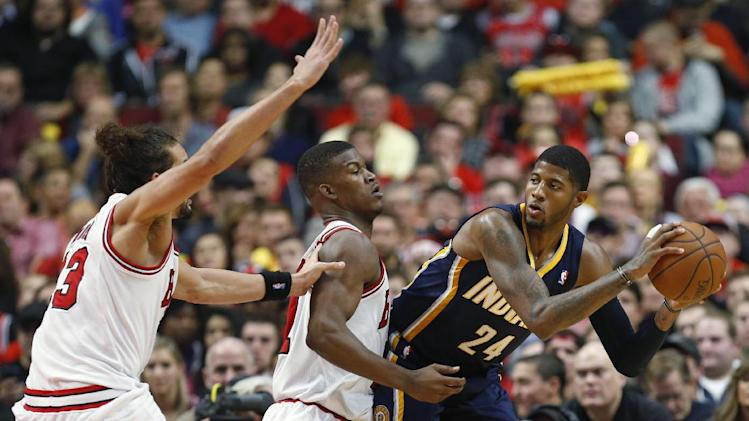 Indiana Pacers forward Paul George, right, is defended by Chicago Bulls guard Jimmy Butler, center, and center Joakim Noah, left, during the second quarter of an NBA basketball game in Chicago, Saturday, Nov. 16, 2013