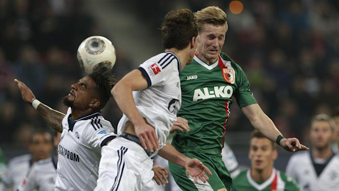 Schalke's Kevin-Prince Boateng of Ghana, background left, teammate Leon Goretzka, foreground and Augsburg's Andre Hahn challenge for the ball during the German first division Bundesliga soccer match between FC Augsburg and FC Schalke 04, in Augsburg, southern Germany, Friday, March 14, 2014
