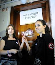 Activists from the European Union of Jewish Students hold up 'No Nazi' symbols in front of Laszlo Csatary's hideaway building, only a few kilometers from his home in Budapest. Hungarian authorities detained, grilled and put under house arrest Csatary, age 97