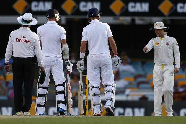 Australia's captain Clarke talks to England's Anderson as batsman Root and umpire Dar look on during the fourth day of the first Ashes cricket test match in Brisbane