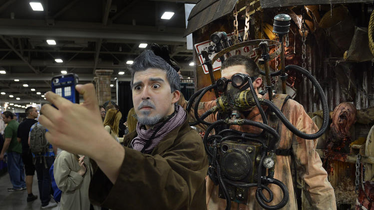 "Jackson Maestas as ""The War Doctor"" makes a selfie with a character on the floor at the opening day of Salt Lake Comic Con, Thursday, April 17, 2014, in Salt Lake City, Utah. (AP Photo/The Salt Lake Tribune, Scott Sommerdorf)"