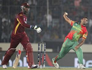 Bangladesh's Rahman bowls as West Indies' Samuels looks on during their ICC Twenty20 World Cup match in Dhaka