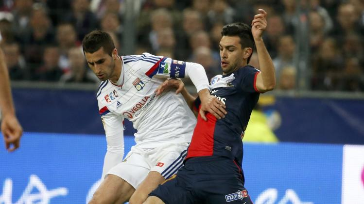 Olympique Lyon's Gonalons challenges Paris St Germain's Pastore during their French League Cup final soccer match at the Stade de France stadium in Saint-Denis