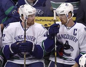 Canucks' Sedin talks with his twin brother Henrik while on the bench during Game 4 of their NHL Western Conference Hockey quarter-final playoff against the Los Angeles Kings in Los Angeles