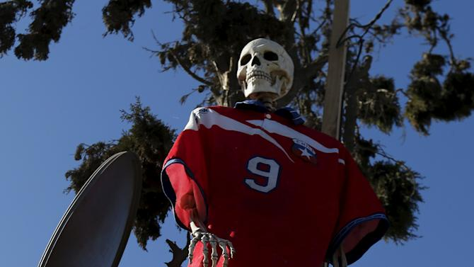 A skeleton doll with a Chilean national soccer team t-shirt is seen outside a bicycle repair shop in La Serena