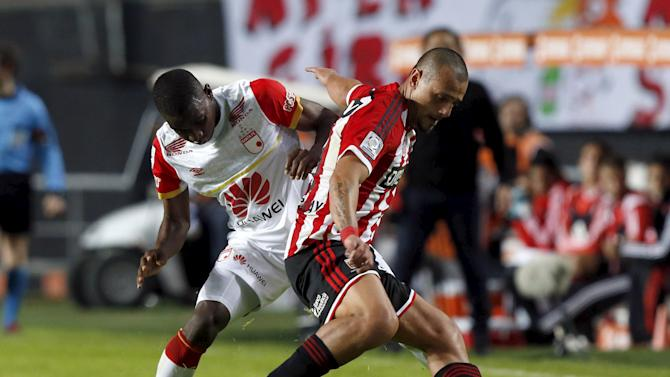 Aguirregaray of the Argentina's Estudiantes de La Plata fights for the ball with Mosquera of Colombia's Independiente de Santa Fe during their Copa Libertadores soccer match in La Plata