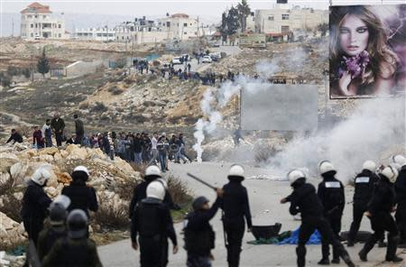 Palestinian policemen (backs to camera) stand in front of demonstrators outside the Jalazoun refugee camp near the West Bank city of Ramallah January 12, 2014. REUTERS/Mohamad Torokman