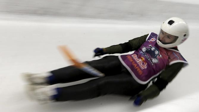 A woman slides down during the shovel race event on the luge and bobsleigh track in Sigulda