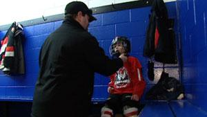 Derek Tubman helps his six-year-old son, Cole, get ready for a Capital City Condors hockey game.