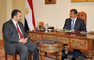 Egyptian President Mohamed Morsi (right) meets with Prime Minister Hisham Qandil on July 24 in Cairo. Qandil has selected a new government in which the finance and foreign ministers from the outgoing cabinet will retain their posts, state television reported on Wednesday