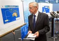 John Young, general manager of the emergency response division of the Australian Maritime Safety Authority (AMSA) walks past a diagram showing the search area for Malaysia Airlines Flight MH370 in the southern Indian Ocean, during a briefing in Canberra March 20, 2014. REUTERS/Sean Davey