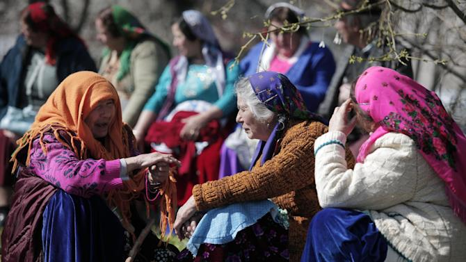 """This Saturday, March 23, 2013  photo shows elderly Roma women from the Kalaidzhi community having a chat during so called """"Roma bridal market"""". The Kalaidzhi, who represent only a small portion of the estimated 700,000 Roma in Bulgaria, are almost all devout Orthodox Christians who keep teenage boys and girls separate. Parents sometimes remove girls from school at 15 or even earlier to keep them from mixing with boys. The isolation is broken only by Internet chats and the twice-a-year bridal fairs.  (AP Photo/Valentina Petrova)"""